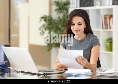 Portrait of a businesswoman working at office reading a letter in a desktop - Stock Photo