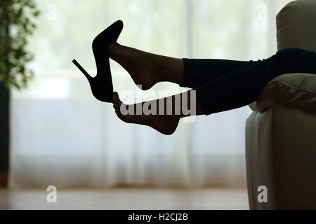 Back light silhouette of a woman resting with feet taking off shoes on a couch at home with a window in the background - Stock Photo