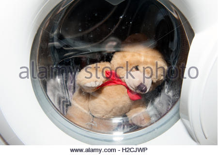 Childs teddy bear in a washing machine. - Stock Photo