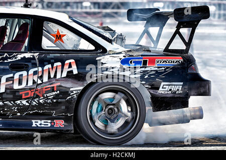 Car drifting auto racing event action with smoking tyres. Pattaya Thailand S. E. Asia - Stock Photo