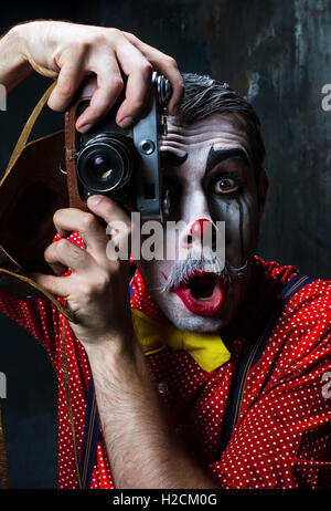 The scary clown and a camera on dack background. Halloween concept - Stock Photo