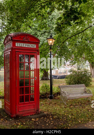 Pre-war 1930's traditional British red telephone box with old lamp post and bench - Stock Photo