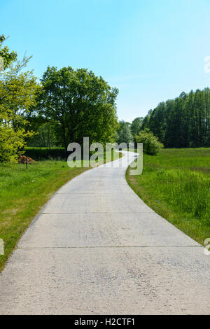Winding country road through green fields and forests in the German countryside in Spring. - Stock Photo