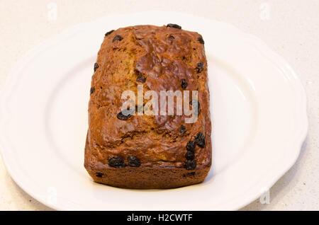 Freshly baked Banana bread with raisins on a white platter - Stock Photo