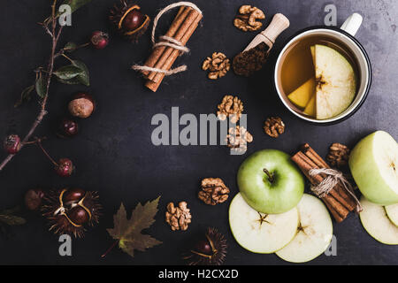 Frame of autumn leaves, chestnuts and ingredients for hot spiced tea and central copy space over rustic table viewed - Stock Photo