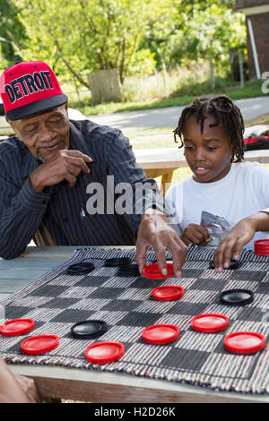 Detroit, Michigan - An elderly man and a young boy team up to play checkers at a block party. - Stock Photo