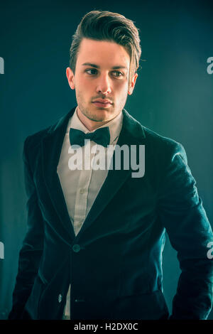 Young businessman confidently posing and looking at camera, wearing suit, on dark background - Stock Photo