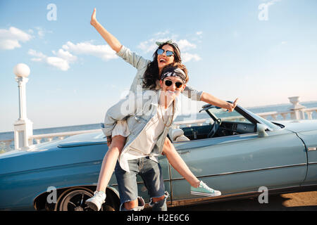 Cheerful young man holding her girlfriend and having fun outdoors - Stock Photo