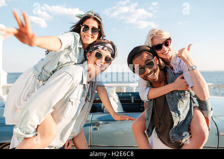 Two smiling young men carrying girls and showing thumbs up in summer - Stock Photo