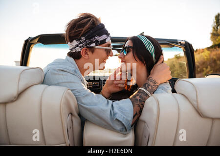Happy young couple kissing in cabriolet in summer - Stock Photo