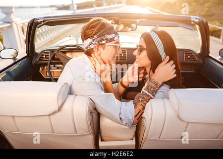 Happy beautiful young couple sitting and kissing in cabriolet in summer - Stock Photo