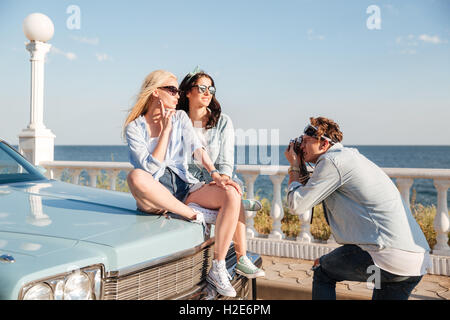 Two beautiful young women sitting on car and posing to man photographer in summer - Stock Photo