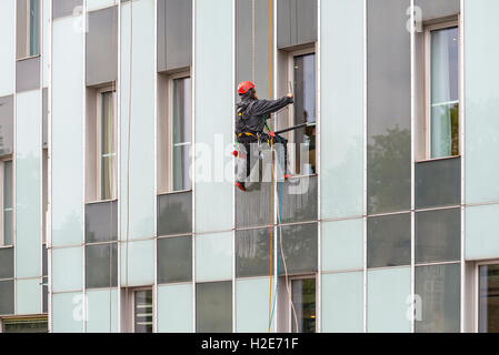 Window cleaner on skyscraper façade, Hamburg, Germany - Stock Photo