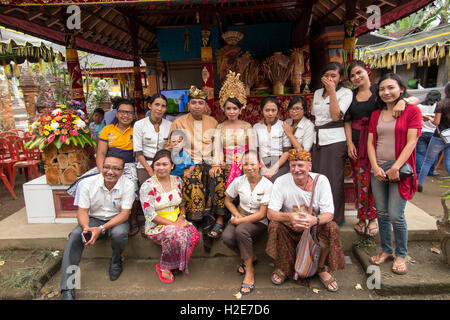 Indonesia, Bali, Payangan, Susut, weddings, group with couple in village house compound and western tourist in sarong - Stock Photo