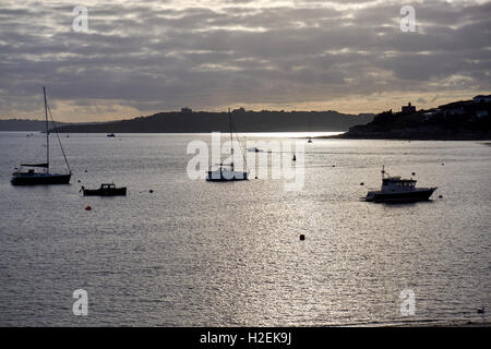 St Mawes Harbour at sunset with fishing boats and yachts, plus St Mawes Castle and Pendennis Castle, Falmouth, in - Stock Photo