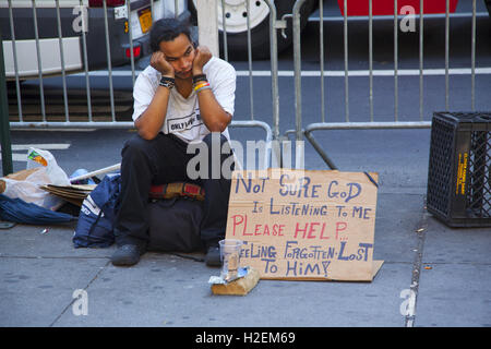 Homeless man who seems to be saying his prayers are not being answered on the street in midtown Manhattan, NYC. - Stock Photo
