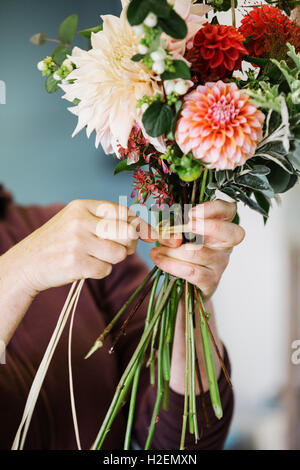 Organic flower arrangements. A woman creating a hand tied bouquet. - Stock Photo
