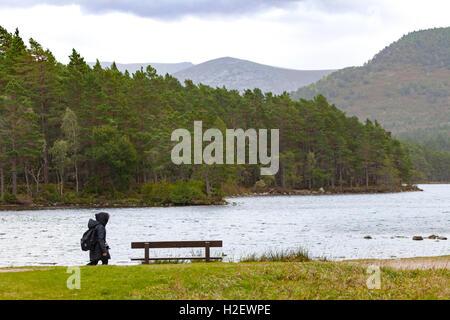 A visitor to Loch an Eilein in the scottish highlands wraps up warm during a walk around the Loch - Stock Photo