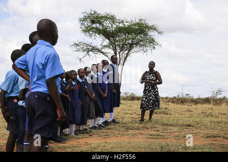Kajiado, Kenya. 28th Oct, 2016. A teacher sings songs with her students during the ceremony for the last day of - Stock Photo