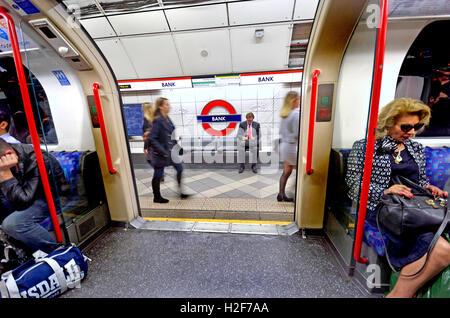 London, England, UK. London Underground tube station: train doors open at Bank station - businessman on the platform - Stock Photo