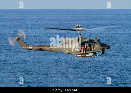 Helicopter hovering. Diver preparing to jump from an Italian Air Force or Aeronautica Militare Italiana Agusta-Bell - Stock Photo
