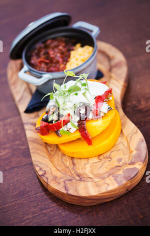 The Red Lion  village public house food dishes. Trencher with a small pot of stew and a stack of fresh vegetables - Stock Photo
