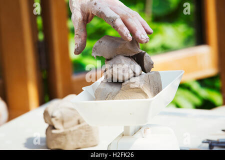 A woman potter working clay on  a potter's wheel in her workshop. - Stock Photo
