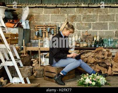 Commercial florist, a woman sitting on  a crate using a digital tablet. Pink and white flowers with green foliage - Stock Photo