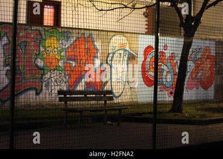 Graffiti, aerosol art in park at night through a fence - Stock Photo