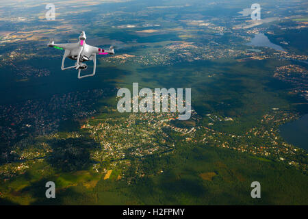 Quadrocopter flying over farmland - Stock Photo