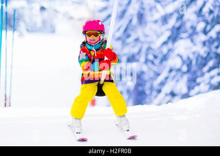 Child skiing in mountains. Active toddler kid with safety helmet, goggles and poles. Ski race for young children. - Stock Photo