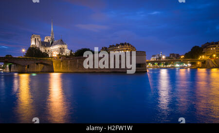 The iconic gothic Cathedral Notre Dame De Paris and the River Seine seen from the Quai de la Tournelle at night - Stock Photo