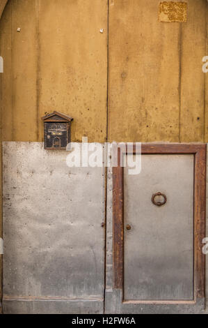 Antique yellow door, mailbox, iron swing, small frame, very heavy. You get into the smaller one. - Stock Photo