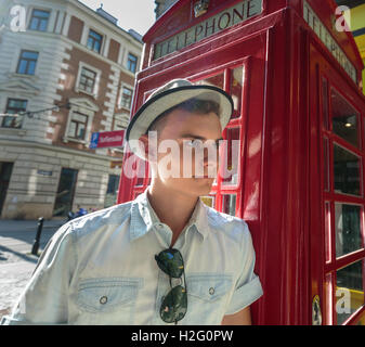 Closeup of a handsome teenager leaning against a red phone box - Stock Photo