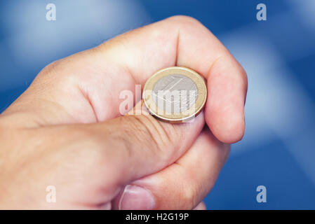 Businessman hand tossing coin to flip on heads or tails, concept of chance, opportunity and decision making - Stock Photo
