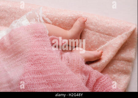Baby feet newborn. Sleeping baby foots on pink sheet of the bed - Stock Photo