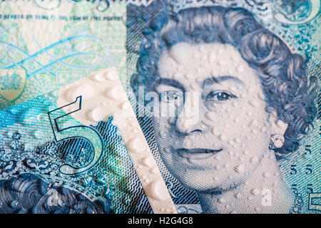 A close up detailed photo of the New waterproof Polymer UK Five Pound Note showing its water resistance - Stock Photo