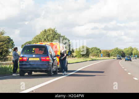 Two young women and car broken down on the A1(M) motorway with AA van - Stock Photo