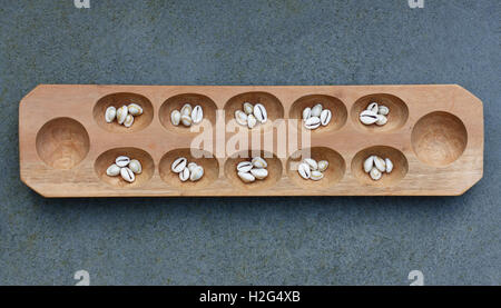 Mancala board with shells. Mancala is a traditional board game played around the world. - Stock Photo