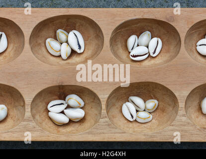 Detail of a mancala board with shells. Mancala is a traditional board game played around the world. - Stock Photo