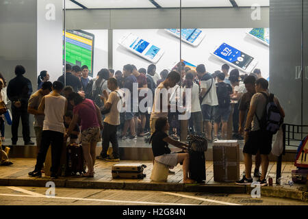 scalpers sell new iPhone 7s outside the Apple Store on Canton Road in Hong Kong to wealthy buyers who don't want - Stock Photo