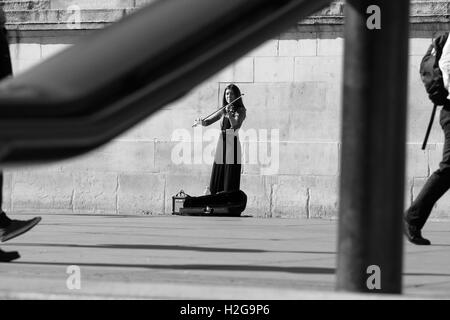 A street entertainer plays her violin in Trafalgar Square, London, England while people walk passed. - Stock Photo