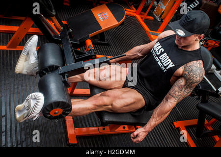 male bodybuilder doing leg curl in the gym - Stock Photo