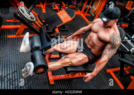 bodybuilder doing  leg curl in the gym - Stock Photo