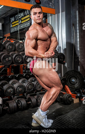 bodybuilder doing competition poses showing defined muscles - Stock Photo