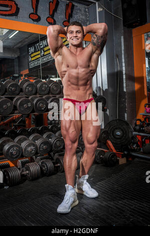 bodybuilder doing competition poses wearing a posing pouch and showing defined muscles - Stock Photo