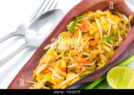 Thai fried noodle or stir-fried Thai style small rice noodles (Pad Thai) on banana blossom with fork and spoon on - Stock Photo