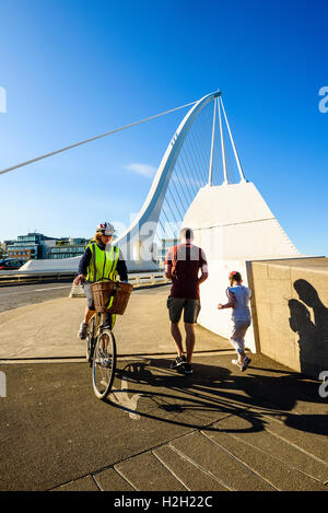 Cyclist and runners at south end of Samuel Beckett Bridge over River Liffey Dublin Ireland - Stock Photo