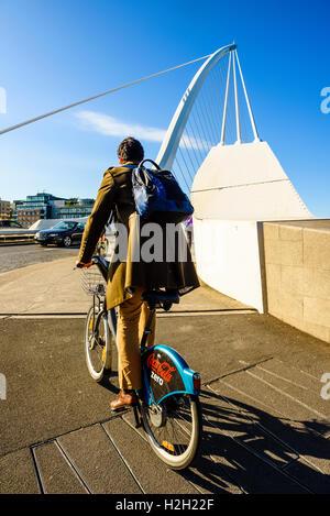Cyclist at south end of Samuel Beckett Bridge over River Liffey Dublin Ireland - Stock Photo