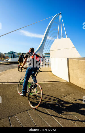 Cyclists at south end of Samuel Beckett Bridge over River Liffey Dublin Ireland - Stock Photo